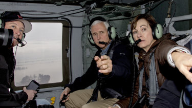 Vice-President Mike Pence and Iowa Governor Kim Reynolds, second right, point to flooded areas, with Nebraska Governor Pete Ricketts, left, during a helicopter flight over areas affected by the flooding of the Missouri and Elkhorn Rivers on Tuesday.