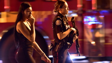 A woman is escorted by police away from the Toronto shooting scene.
