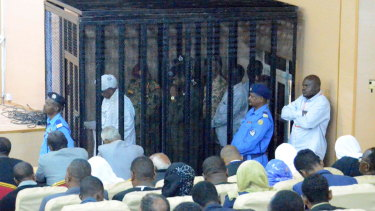Omar al-Bashir, pictured in white in the cage, returned to court on August 19 to answer corruption charges.