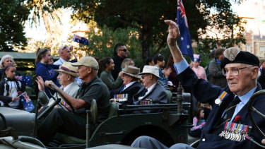 Korean War veterans wave to parade attendees as they drive down St Georges Terrace in a historical car.