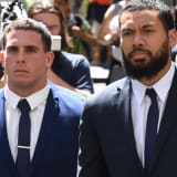 NRL players Adam Elliott and Asipeli Fine leave the Downing Centre Court pm Monday.