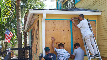 Employees of the Island Root Kava Lounge board up the windows of the business in preparation for Hurricane Dorian in Melbourne, Florida.