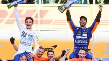 Lando Norris and Daniel Ricciardo celebrate with the McLaren crew.