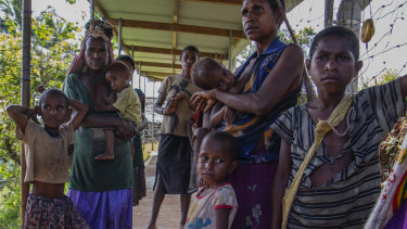 Families wait at a health clinic in Papua New Guinea. Australia has increased its aid spending in Pacific region this financial year.