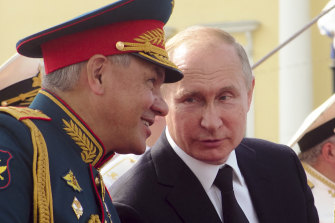 Russian Defence Minister Sergei Shoigu speaks to President Vladimir Putin during celebrations in St Petersburg in July.