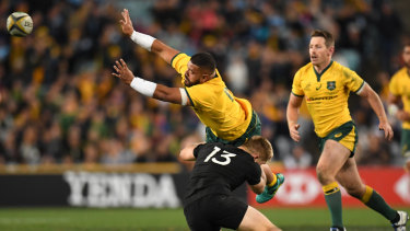 Bruising: Jack Goodhue goes low and hard into the legs of Tolu Latu during the Bledisloe Cup opener in Sydney.