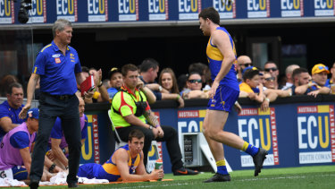 West Coast defender Jeremy McGovern leaves the field for treatment.
