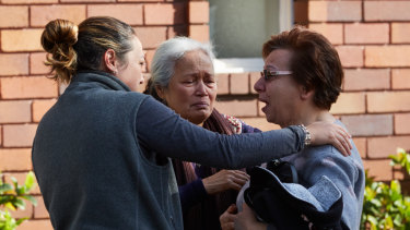 The owner of the property in Waverley is consoled after an elderly woman died in a fire in her home.