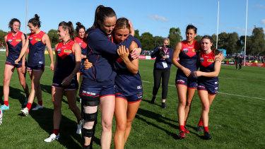 Daisy Pearce, wearing a leg brace, hugs teammate Eliza McNamara after the Demons defeated the Lions.