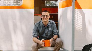 Brick builder Ben Craig sitting in the Lego caravan that took about five months to build.