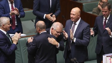 Treasurer Josh Frydenberg is congratulated by Prime Minister Scott Morrison and other colleagues after delivering his budget speech.