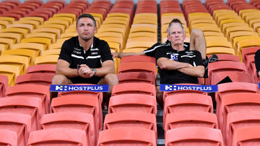 Rugby league in the coronavirus age: Souths' Sam Burgess and Wayne Bennett swap the coaches' box for the grandstand at an empty Suncorp Stadium on Friday night. When there were still games being played.