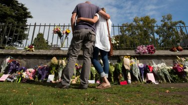 People pay their respects at a floral tribute at the Christchurch Botanical Gardens.
