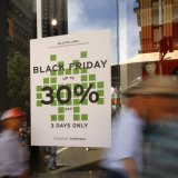 Pedestrians walk past in front of a Black Friday sale advertisement in Sydney, Australia.
