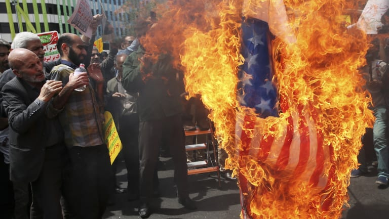 Iranian protesters burn a representation of the US flag in Tehran after Trump announced the US was pulling out of the Iran nuclear accord last week.
