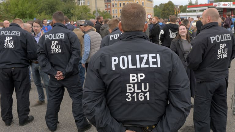 Police officers observe right-wing demonstrators during a far-right demonstration in Chemnitz, Germany.