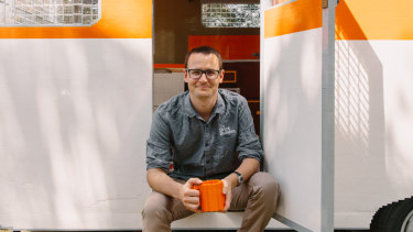 Brick builder Ben Craig sitting in the Lego caravan that took about five months to build.