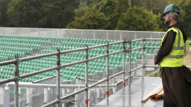Capuchin priest friar Bryan Shortall from Dublin looks out from the wet stage during preparations are underway to build the stage for the Pope in Phoenix Park, Dublin.