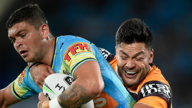 Gold Coast's Ashley Taylor is tackled by the Broncos' Alex Glenn.