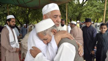 Pakistani Muslims greet each other after offering Eid al-Fitr prayers in Peshawar.
