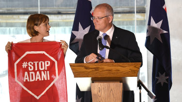 An Adani protester takes to the stage during a Brisbane speech by Prime Minister Scott Morrison this month.
