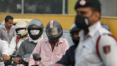 Motorcyclists cover their faces to save themselves from air pollution as they wait at a crossing in New Delhi, India.