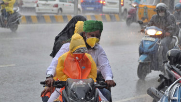 An Indian family wearing face masks navigate monsoon rains in Hyderabad, India.