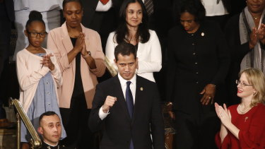 Juan Guaido, centre, stands up as Donald Trump introduces him during his third State of the Union address.