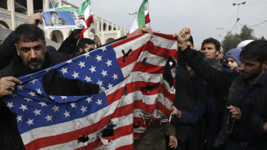 Protesters burn an American flag during a demonstration over the US killing of Qassem Soleimani in Tehran on Friday.