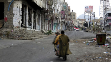 Men ride through streets wrecked by fighting in Taiz, Yemen in this February.