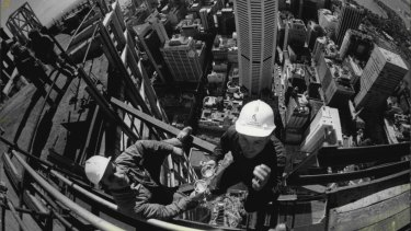 Cheers … A fisheye lens view from the top of Centrepoint tower as riggers, Mr Stan Kowalski of Randwick (left) and Mr Albert Fortini of Lidcombe, celebrate the tower's rising past the MLC Centre.