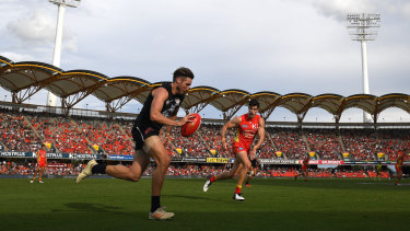 Still got the Blues: Carlton's Dale Thomas races up the wing at Metricon Stadium on the Gold Coast as Suns' Ben Ainsworth closes in.