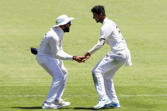 India's Rohit Sharma, left, and teammate Washington Sundar, right, celebrate the dismissal of Australia's Steve Smith.