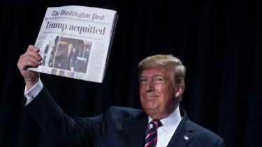 President Donald Trump holds up a copy of the Washington Post during the annual National Prayer Breakfast a day after the Senate voted not to remove him from office.