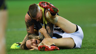 Dustin Martin tangles with Collingwood's James Aish.