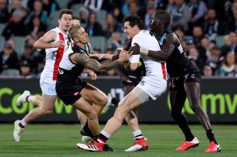 Hamish Hartlett and Aliir Aliir tackle Jake Carlisle