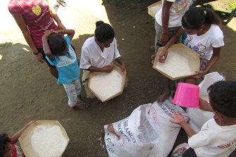 Children sifting rice at the Topu Honis children's shelter in Kutet, East Timor, in 2010.