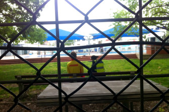 A police officer and lifeguard seen through the fence of the Fitzroy pool following a reported drowning there today.