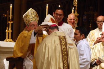 George Pell ordains Peter Comensoli as bishop in 2011.