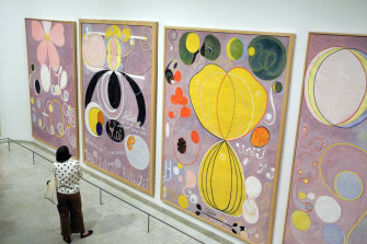 An art lover is dwarfed viewing four  works of The Ten Largest  series at the Guggenheim in 2018, the gallery's best-attended ever show.
