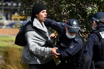 Victoria Police members arrest a protester along the St Kilda foreshore.