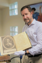 Fryer Library manager Simon Farley holding the rare Captain James Cook book to be auctioned at the University of Queensland.
