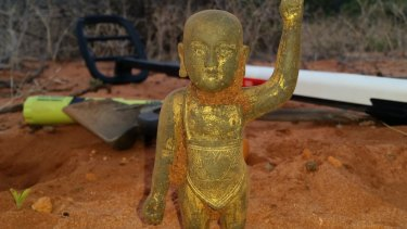 The front of the figurine, with the metal detector in the background.