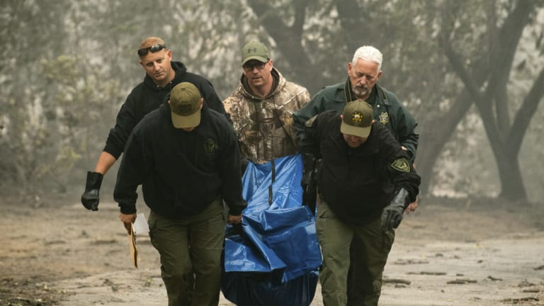 Sheriff's deputies recover the remains of a victim of the Camp Fire.