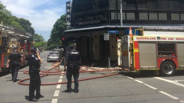 Fire crews close the intersection outside the Port Office Hotel in Brisbane to fight a blaze at the pub.