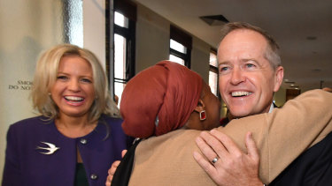 Opposition Leader Bill Shorten hugs Hawa Del as his wife Chloe Shorten  looks on during the launch of Labor's policy to lift the equality of Australian women at the Queen Victoria Women's Centre in Melbourne on Friday.