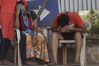 Relatives of a person who died of COVID-19 mourn outside a hospital in Mumbai, India.