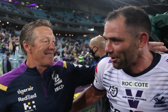 Finally cracking a smile ... Craig Bellamy with Cameron Smith after the grand final triumph.