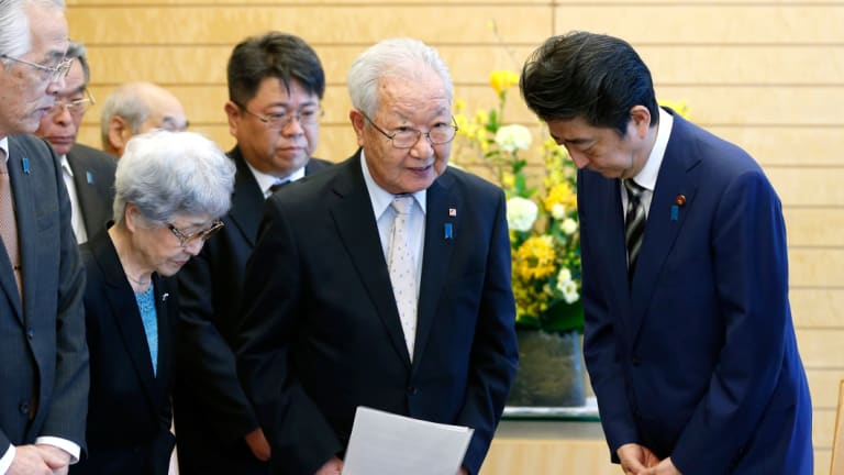 Japanese Prime Minister Shinzo Abe, right, meets with Shigeo Iizuka, second from right, leader of a group of families of Japanese abducted by North Korea, and Sakie Yokota, second from left, mother of Megumi Yokota, one of the Japanese abductees and other members at Abe's official residence in Tokyo in March.