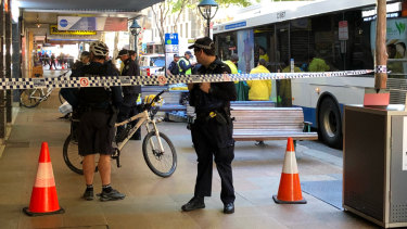 Police cordon off part of Adelaide Street in Brisbane after a woman was hit by a bus on Monday.
